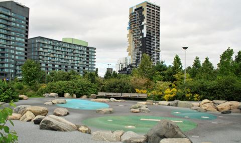 safety surface play area with embedded natural boulders. Benches at far side with trees and shrubs behind. Tall apartment buildings in background